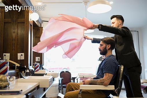 Barber flipping smock over customer in barber shop - gettyimageskorea