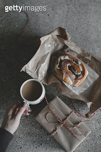 Coffee Mug with Cinnamon Bun Wrapped in Brown Paper - gettyimageskorea