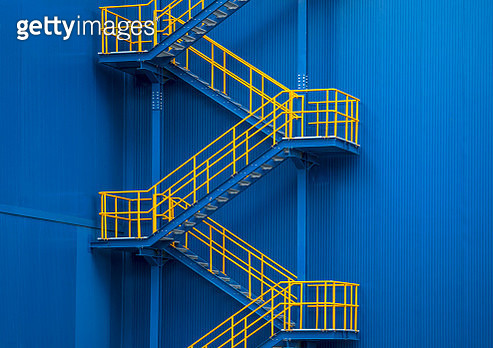 Yellow metal staircase against a blue wal - gettyimageskorea