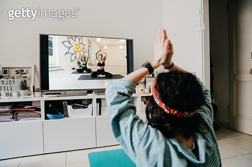 Woman practicing yoga at home with a video lesson on the TV. She's at home during the Coronavirus Covid-19 quarantine. - gettyimageskorea