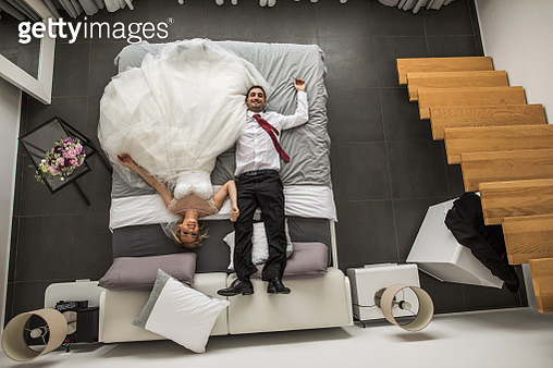 Above view of newlyweds relaxing on a bed in their bedroom. - gettyimageskorea