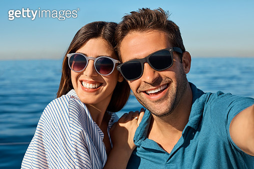 Shot of a young couple taking a selfie together on an ocean cruise - gettyimageskorea
