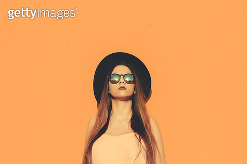 Portrait Of Young Woman Wearing Sunglasses And Hat Against Orange Background - gettyimageskorea