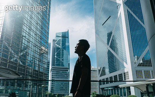 Silhouette of professional young businessman standing against contemporary financial skyscrapers and looking up into sky with positive emotion - gettyimageskorea