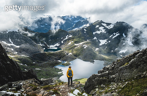 Woman overlooking dreamy valley in Norway. - gettyimageskorea