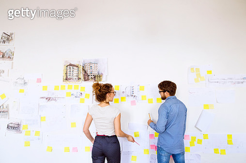 Two young architects consulting a project together. Designers and team workers in creative office. - gettyimageskorea