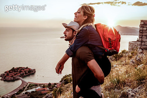 Happy couple hiking together in mountains with backpacks - gettyimageskorea