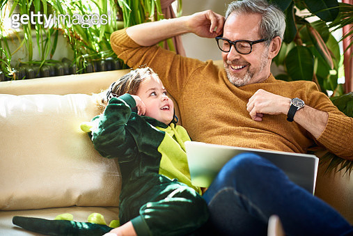 Modern grandfather sitting with granddaughter having fun and relaxing, childcare, connections, role model - gettyimageskorea