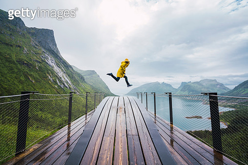 Norway, Senja island, man jumping on an observation deck at the coast - gettyimageskorea