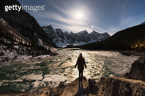 A lone figure in the moonlight at Moraine Lake, Banff National Park, Alberta, Canada - gettyimageskorea