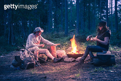 man and women in the forest by the campfire - gettyimageskorea