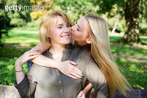 Adult daughter kissing mother in park - gettyimageskorea