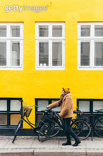 Young woman in yellow hat and fake fur holding bike against yellow wall - gettyimageskorea