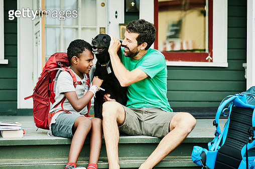 Father and son sitting on front porch of home with dog before going on backpacking trip - gettyimageskorea