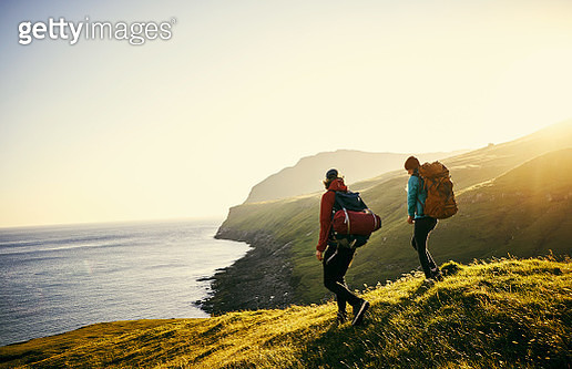 Shot of a young couple hiking through the mountains - gettyimageskorea