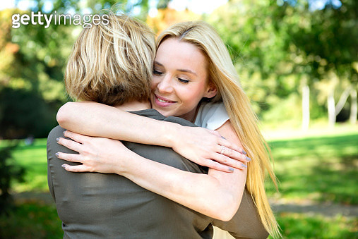 Mother and adult daughter embracing in park - gettyimageskorea