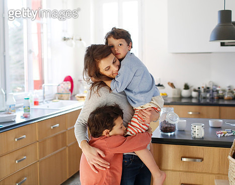 A mom hugging her sons in the kitchen - gettyimageskorea