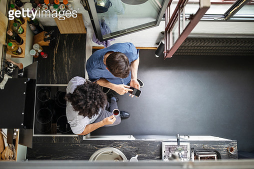 Top view of businessman showing smart phone to male colleague. Male professional with curly hair drinking coffee and looking at mobile phone of coworker. - gettyimageskorea