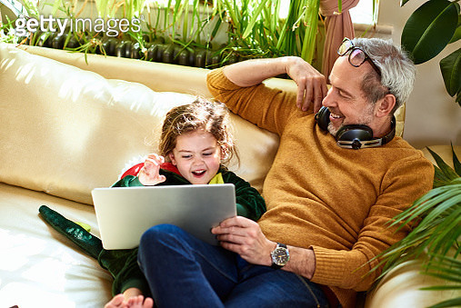 Mature father watching online tv with daughter in dinosaur costume - gettyimageskorea