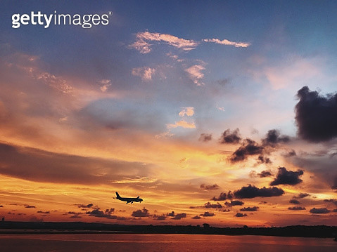 Stunning Orange Evening Sunset And Plane Flying In The Sky In Island Bali - gettyimageskorea