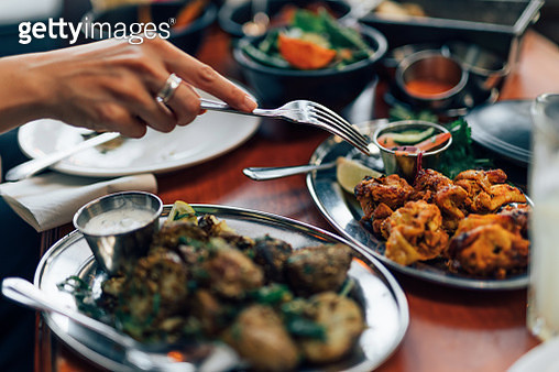 Close up of woman eating Chicken Tikka with fork - gettyimageskorea