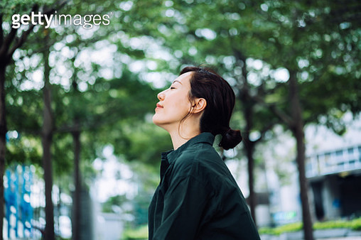 Young Asian businesswoman taking a break in urban park in the city. Enjoying the gentle breeze with her eyes closed, resting in the middle of a work day - gettyimageskorea
