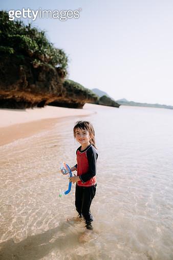 Portrait of 4 year old girl holding snorkel mask, standing on tropical beach, Ishigaki Island of the Yaeyama Islands National Park, Okinawa, Japan - gettyimageskorea