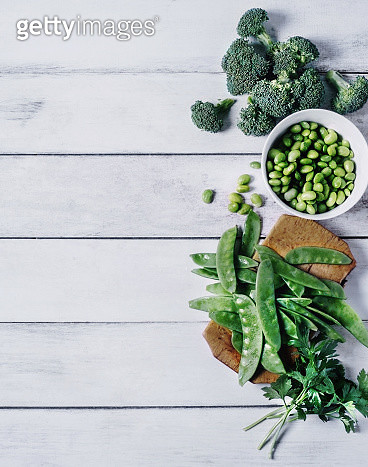 Fresh vegetables (edamame, sugar snap peas, parsley and broccoli) on white, wooden background - gettyimageskorea