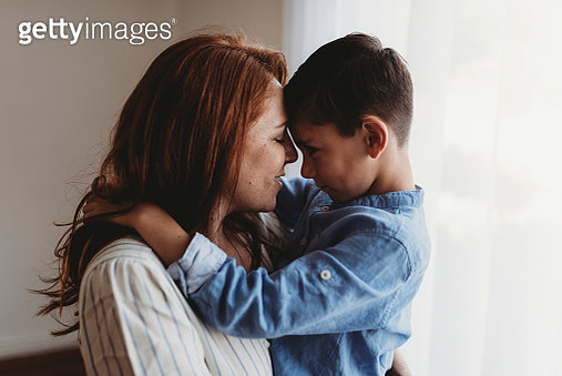 Side view of young mother embracing young boy in studio - gettyimageskorea