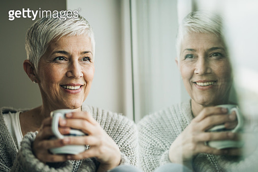 Portrait of smiling mature woman with coffee cup relaxing by the window. - gettyimageskorea