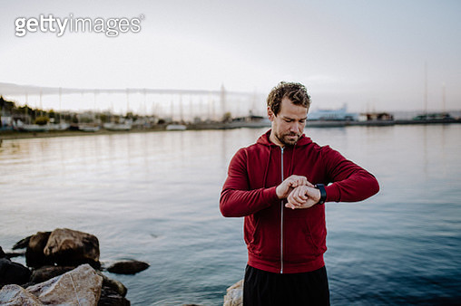 A fit mature sportsman runner standing outdoors on beach, using smartwatch. - gettyimageskorea