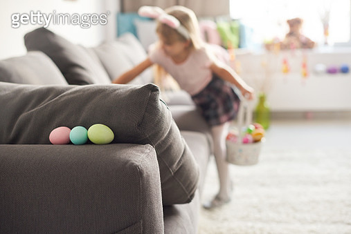 Girl searching for easter eggs on sofa - gettyimageskorea