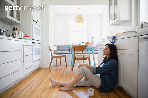 Serene brunette woman sitting kitchen floor eyes closed - gettyimageskorea