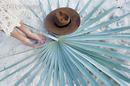 Top view on female feet, brown hat and palm leaf on white sand - gettyimageskorea