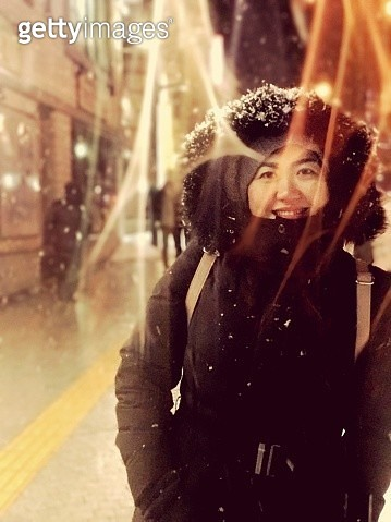 Portrait Of Mid Adult Woman In Warm Clothing Standing On Street At Night During Snowfall - gettyimageskorea