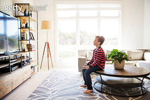 Boy sitting on table and playing video game at home - gettyimageskorea