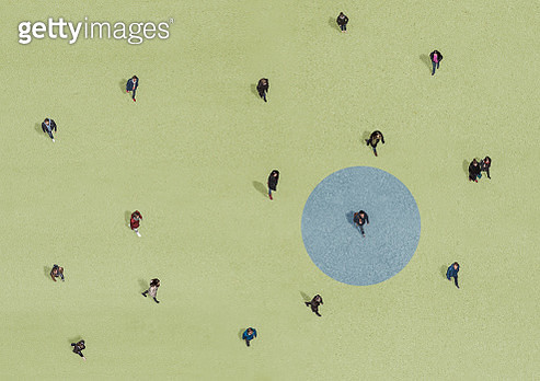 Group of people walking on green ground with blue circle - gettyimageskorea