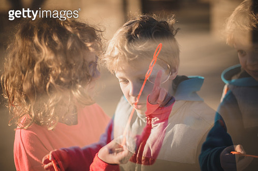 Double Exposure of Children Blowing Bubbles - gettyimageskorea