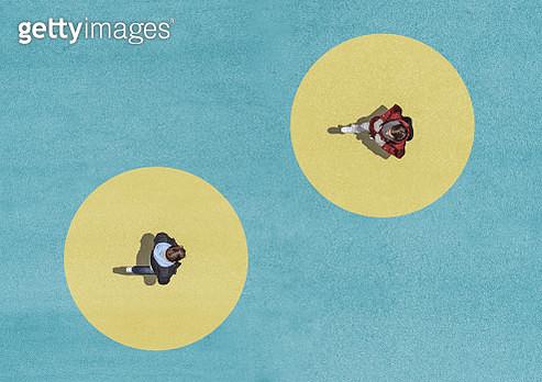 Two men walking on yellow circles. - gettyimageskorea