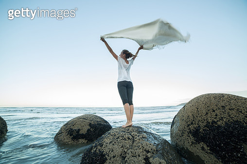Young woman stands on a boulder at Moeraki boulders, holds a blanket in the air. - gettyimageskorea