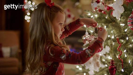 Close up of girl decorating Christmas tree with illuminated lights - gettyimageskorea