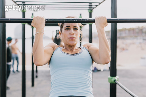 Woman Doing Pull-Ups on Monkey Bars for Fitness - gettyimageskorea