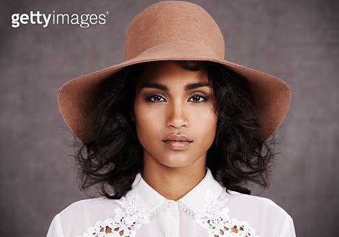 Cropped portrait of a stylish young woman wearing a hat standing against a gray background - gettyimageskorea