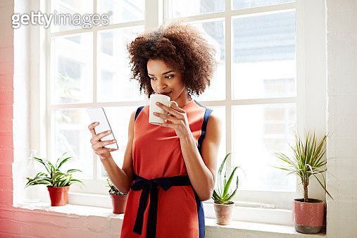 Woman drinking coffee and checking her phone - gettyimageskorea