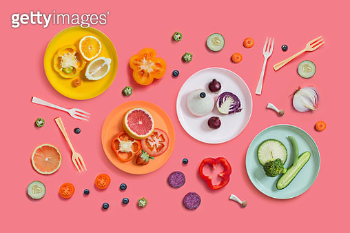 Minimalist style healthy eating colourful sliced vegan food in multi coloured plates served on pink background. - gettyimageskorea
