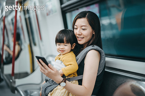 Young mother with cute little daughter using and looking at smartphone with joy while riding on subway - gettyimageskorea