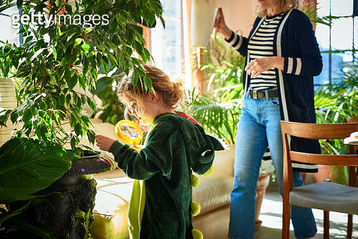 Cute child in dragon costume investigating leaves at home with mother in background, scrutiny, discovery, little explorer, STEM - gettyimageskorea