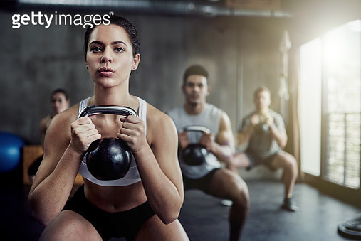 Shot of a fit young woman working out with a kettle bell at the gym - gettyimageskorea