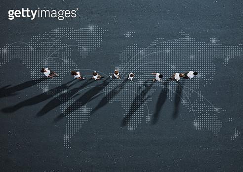 School children in uniforms walking in row across world map - gettyimageskorea