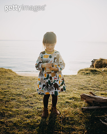 Cute toddler girl looking at her seashell collection - gettyimageskorea